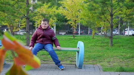 expectancy : Happy boy sitting on a bench in the Park and laughing in park. Slow mo