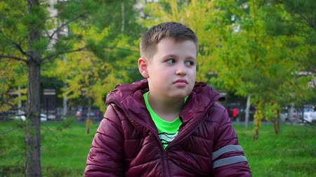 kidnapping : Boy sitting in the Park on a bench. Hes lost, waiting for his parents. Slow-mo Stock Footage