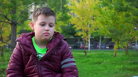 kidnapping : Portrait of a sad boy. Sitting in the Park, hes lost. Slow-mo