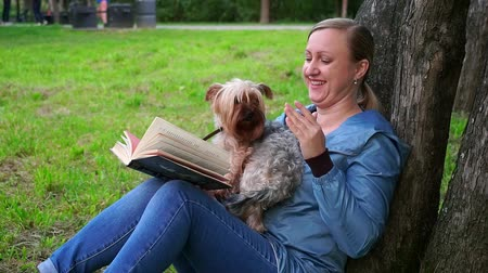 duruş : Attractive woman reading a book in a Park by a tree. A cute dog runs to her