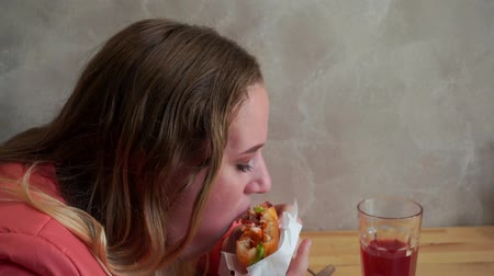 houska : A young hungry girl eating a hamburger. Sitting at a table in a cafe