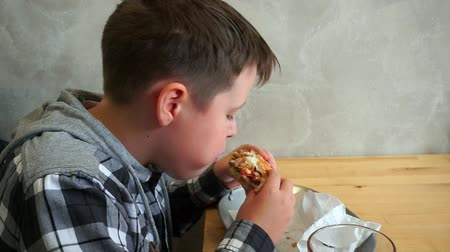 gyerekes : A teenager in a cafe eating a hamburger. He is hungry, tasty and juicy hamburger
