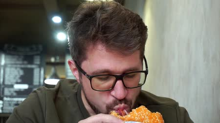starving : Hungry bearded man with glasses eating a delicious hamburger. Slow-mo