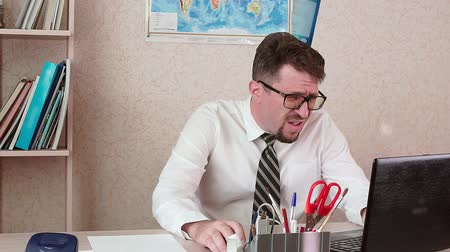 betrokken : A man is an office worker with a beard and glasses working at a laptop