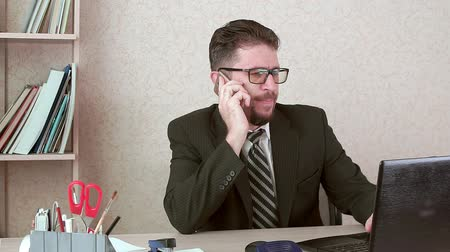 istek : Man office worker with a beard and glasses talking to a client on a smartphone.
