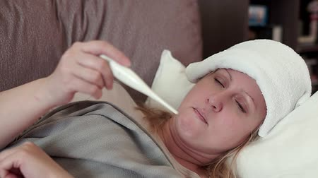 medical thermometer : A middle-aged woman lying on the couch. It measures temperature.
