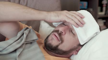 medical thermometer : Bearded man holding his head. He has a cold, chills, headache lying on the couch