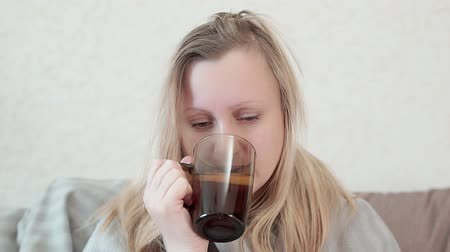 kaszel : Woman with a cold, flu, drink warm tea with lemon. She is sick, fever, chills