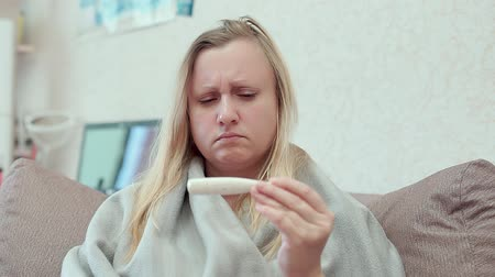 horečka : A woman looks at the medical thermometer, sitting on the couch in a blanket. Dostupné videozáznamy