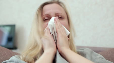 handkerchief : The woman blows her nose in a paper handkerchief. She has a cold, headache