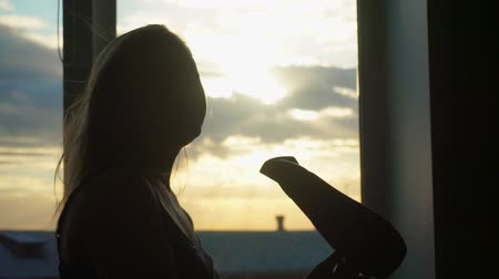 cama : A middle-aged woman dries hair dryer at sunset. She sings and dances. Stock Footage