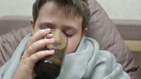 medical thermometer : The boy drinks medicine and tea with lemon. Hes got a cold Stock Footage