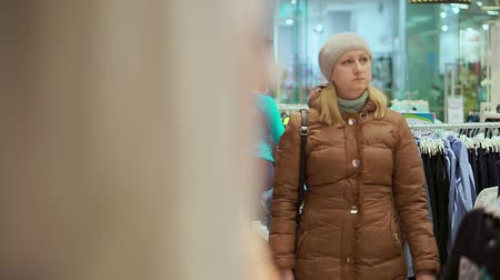 fitting : A middle-aged woman in a winter coat and a hat goes to a childrens clothing store. Fits the camera.