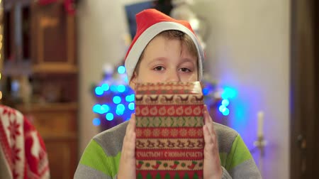 megragad : Boy teenager in a sweater holds out a gift and smiles. On the background of Christmas lights Stock mozgókép