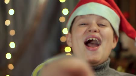 nativo : The boy in the sweater and the hat of Santa Claus laughs. Close-up, against the background of Christmas lights.