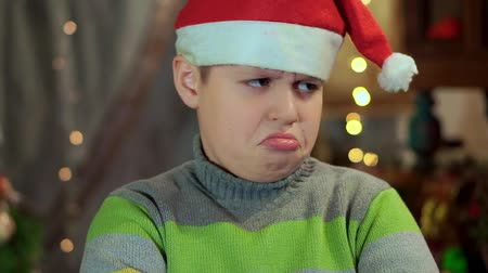 arrabbiato : The boy in the sweater and the hat of Santa Claus is upset and offended. He has no gift. Close-up, against the background of Christmas lights