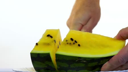 A mans hand cuts a juicy yellow watermelon into pieces. Stok Video