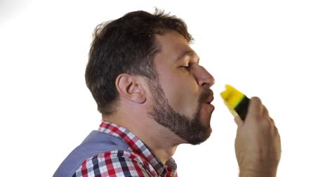 A bearded man bites a slice of juicy yellow watermelon.