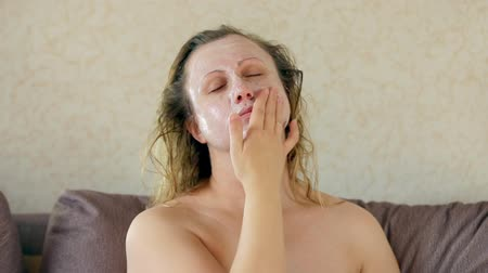 A middle-aged woman with a moisturizing mask on her face Stok Video