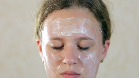 Teen girl putting a moisturizing mask on the face. Stok Video
