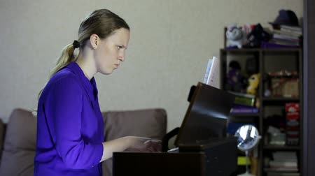 Teen girl plays on the keyboard of the digital piano.