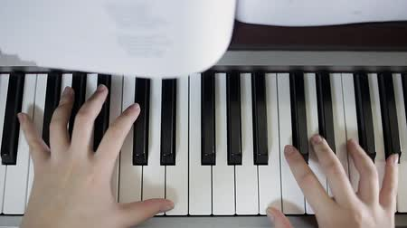 Teen girl plays on the keyboard of the digital piano. Close-up
