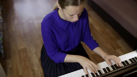 rehearsing : Teen girl plays on the keyboard of the digital piano.
