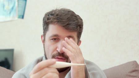 A man measures his temperature and looks at the medical thermometer Stok Video