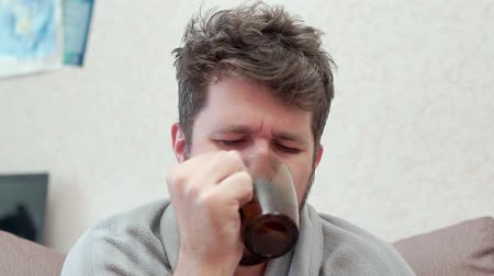 A man drinks tea with lemon and coughs. He has a cold, headache, fever, chills