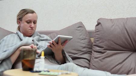 febre : A woman has a cold at home. Lying on the couch with a tablet