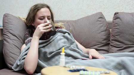 medical thermometer : Teen girl drinking medicine tea warm. Lying on the couch, covered with a blanket