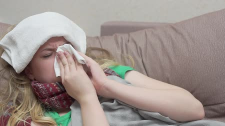 Teenage girl blows her nose in a paper handkerchief. She has a cold