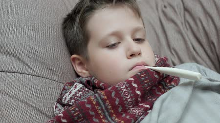 coughing : The boy in the scarf itself measures the house temperature. Hes got a cold Stock Footage