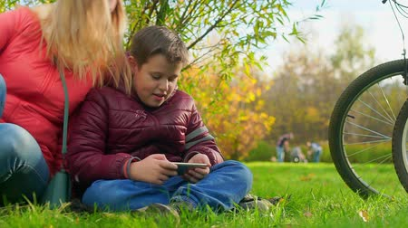 Teenager sitting on the grass, playing smartphone. Mom sat down. Stok Video