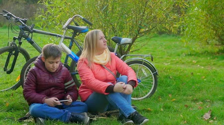 Teen boy sitting on the grass and playing smartphone. Sitting next to mom Stok Video