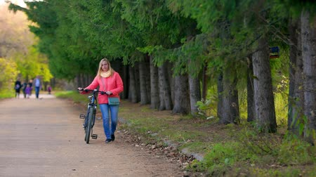 Woman walking with a Bicycle in the Park.She goes to the cameras in the distance