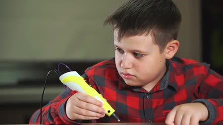 filamento : A boy teenager in a plaid shirt draws a 3D plastic figure with a pen.