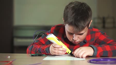 A boy teenager in a plaid shirt draws a 3D plastic figure with a pen.