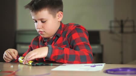 filamento : A teenager boy in a plaid shirt cuts off a piece of ABS plastic for a 3D pen. Stock Footage