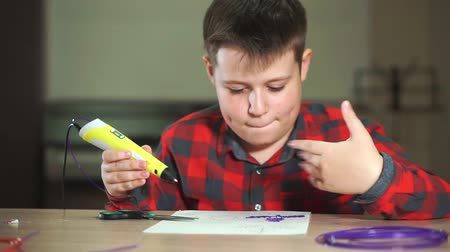 filamento : Boy teenager in a plaid shirt draws a 3D pen.