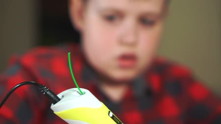 filamento : Close-up teen boy uses 3D pen. He creates a plastic 3D figure.