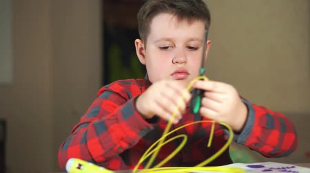 filamento : Teen boy cuts off a piece of yellow ABS plastic for 3D pens. He creates a plastic 3D figure. Stock Footage