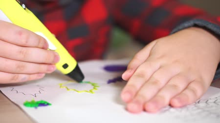 filamento : Boy teenager draws a plastic figure yellow leaf. He uses a 3D pen.