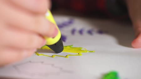 filamento : Extra close-up boy teenager draws a plastic figure yellow leaf. He uses a 3D pen.