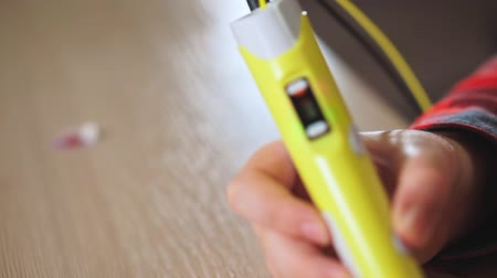 filamento : Teen boy inserts a piece of yellow ABS plastic in a 3D pen. He creates a plastic 3D figure. Stock Footage