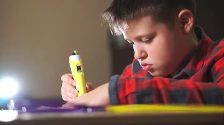 kreativitás : A boy teenager in a plaid shirt draws a 3D plastic figure with a pen.
