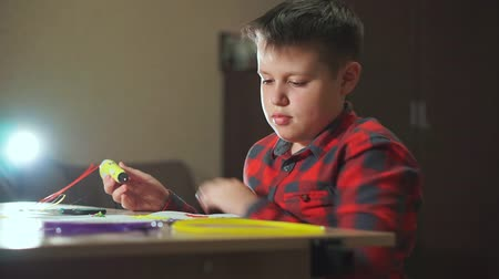 filaman : A boy teenager in a plaid shirt draws a 3D plastic figure with a pen.