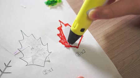 filamento : Close-up boys hand uses a 3D pen. He creates a plant leaf from red ABS plastic. Stock Footage
