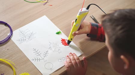 filamento : Teen boy uses a 3D pen. He creates a plant leaf from red ABS plastic. Stock Footage