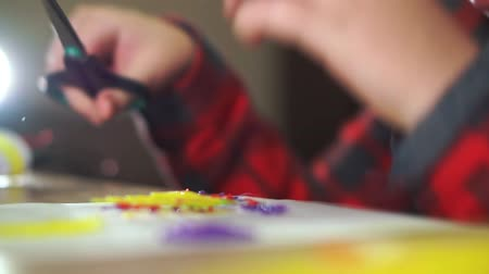 filamento : A teenager boy cuts off excess plastic with scissors. He creates a 3D figure from plastic. Stock Footage